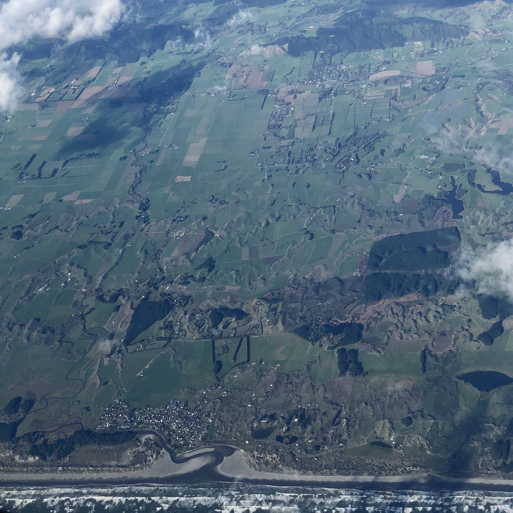 Photo from a plane of waves, beach, river, and farmland.